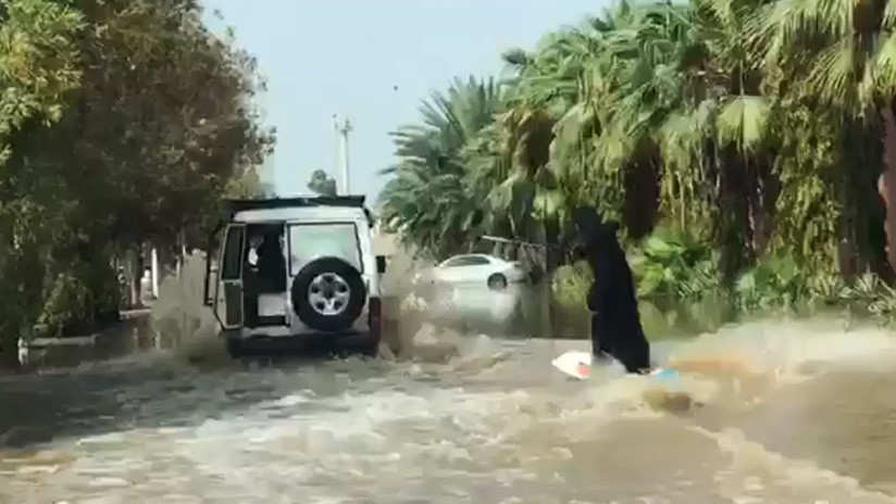Mujer en burka surfea sobre calle inundada en Arabia Saudita